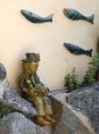 Vodník s kaprem na skalce s hejnem ryb